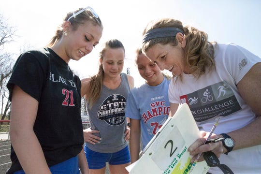 Abbey Mohan looks over some race plans with Zane Trace track coach Jennifer Johnston and fellow runners during practice Tuesday afternoon.