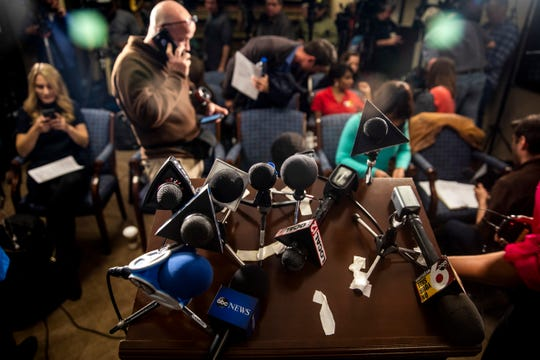 Local and national reporters grab their microphones after the press conference regarding Brian Michael Rini, who claimed to be missing boy Timmothy Pitzen, at the U.S. Attorney's Office in downtown Cincinnati Friday, April 5, 2019.