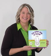 """Beth Gully, shown with her newly released """"The Other Side of Easter"""" book, is one of 94 professionally recognized ambigram designers in the world."""