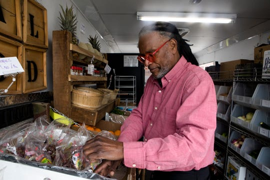 Lemuel Israel, Healthy Harvest Mobile Market manager, organizes produce at the trailer during a stop in Walnut Hills, one of 10 it makes during a week to alleviate the effects of food deserts in several area communities.