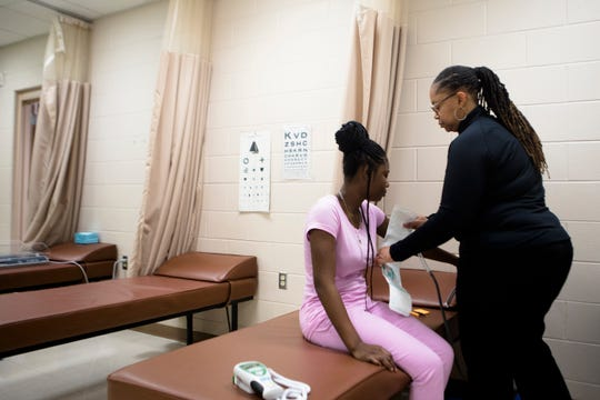 Cahleana Wright, 14, has her blood pressure taken by Felicia Pleasant at Children's Hospital's clinic at South Avondale School in Cincinnati on Thursday, April 4. Cahleana has been seen at the clinic since she was an elementary school student at the school.