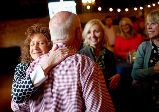 Lisa Roberts, left, embraces Billy Atkins at his arrival at the surprise retirement party for Atkins from Legends Bank at The Belle Hollow in Clarksville, Tenn., on Thursday, April 4, 2019.