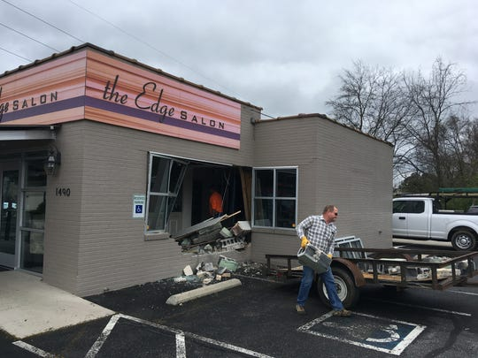 Crews remove debris after a truck crashed into The Edge Salon on Madison Street on Friday, April 5, 2019.