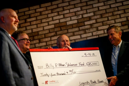 Billy Atkins and representatives from Austin Peay hold up a large fake check to represent the scholarship named in his honor at the surprise retirement party for Atkins from Legends Bank at The Belle Hollow in Clarksville, Tenn., on Thursday, April 4, 2019.