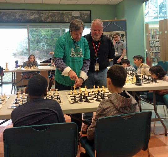 Freeholder Director Brian D. Levine plays simultaneous chess with 11 members of the Franklin Township Chess Club. Tournament arbitrator Ismael Cartagena looks on as Levine makes his move.