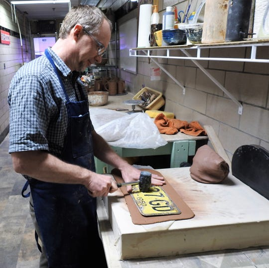 John Miller pounds a license plate into a clay slab to make an impression. It the beginning of the process John uses to make mugs, shot glasses and flasks he sells through Crow House Pottery.