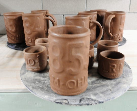 Hand-thrown clay mugs are left to dry before being placed in a kiln and fired.