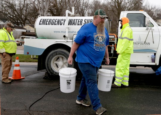 In this photo from April 3, 2019, Adam Wilson of Glenwood, Iowa, walks away with buckets filled with water from Omaha's Municipal Utilities District's emergency water supply tanker, in Glenwood, Iowa. Several communities along the Missouri River continue to struggle to restore drinking water service weeks after massive flooding disrupted life in the towns and caused significant damage.
