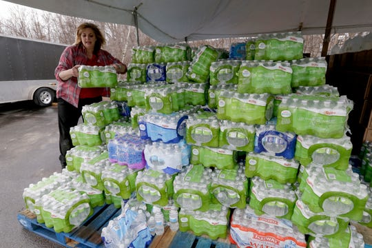 In this photo from April 3, 2019, a resident picks up water bottles donated for flood victioms, in Glenwood, Iowa. Several communities along the Missouri River continue to struggle to restore drinking water service weeks after massive flooding disrupted life in the towns and caused significant damage.