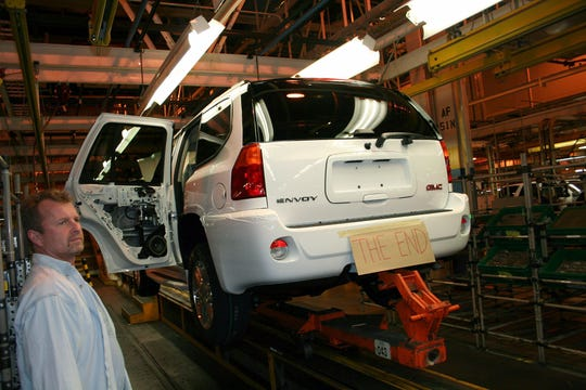 In this picture provided by GM worker Kim Clay, an unidentified employee watches as the last sport utility vehicle, a GMC Envoy, rolls down the assembly line the GM Moraine Assembly plant in Dayton, Ohio on Tuesday, Dec. 23, 2008, during the final shift at the plant. The last SUV rolled off the line at 3:48 pm, ending a production run that began in 1982 and leaving over 1,000 employees at this production line without a job. (AP Photo/Kim Clay)
