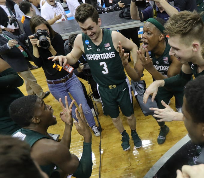 Foster Loyer, left, Cassius Winston, right,  and teammates celebrate Michigan State's 68-67 win against Duke in the East Region final, Sunday, March 31, 2019 at Capital One Arena in Washington, D.C.
