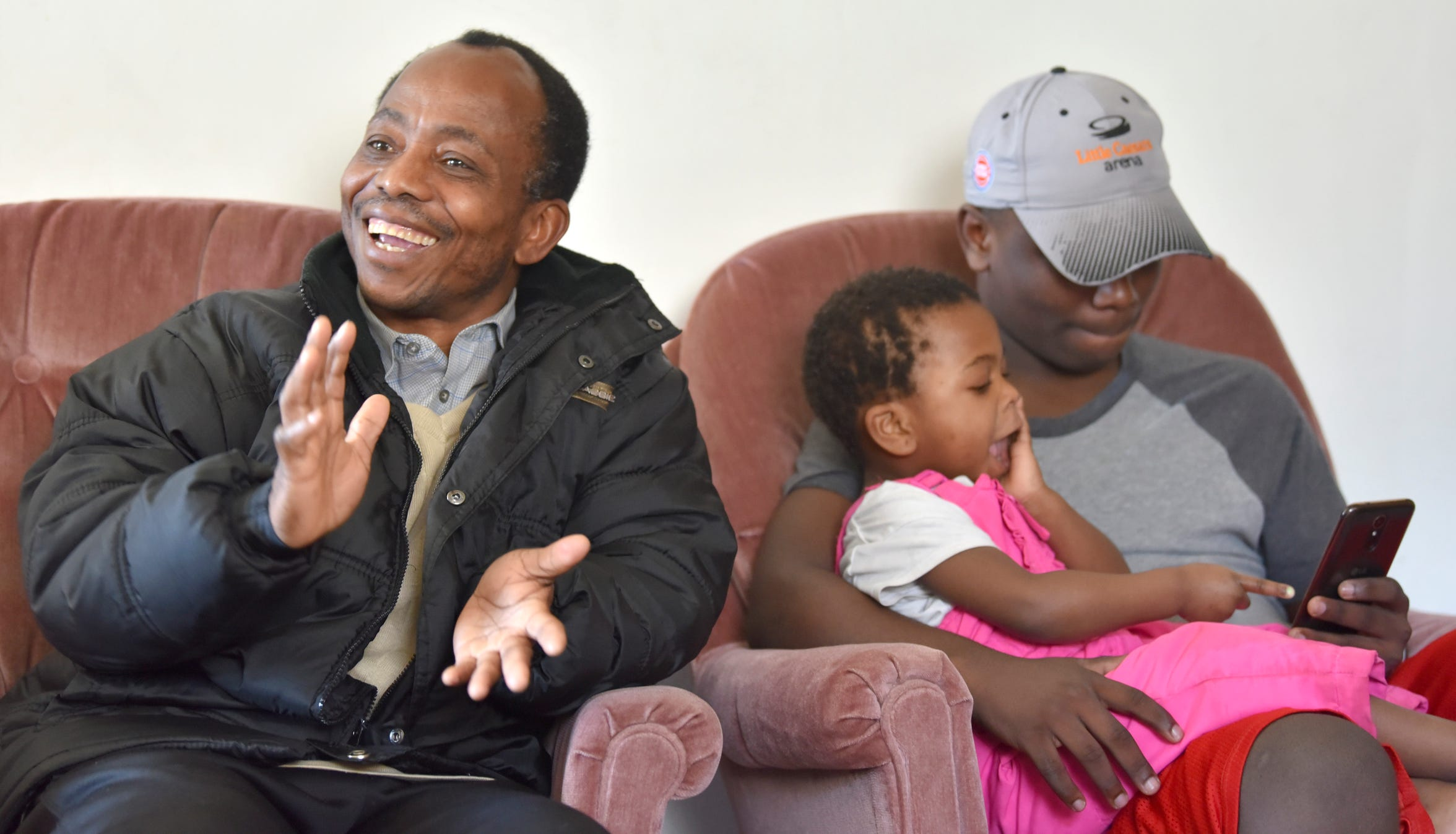 Riobert, left, talking through an interpreter, describes the differences of the U.S. from the Dem. Rep. of Congo as his son, Msimbi, and granddaughter, Neewa, look at the 16-year-old's cell phone.