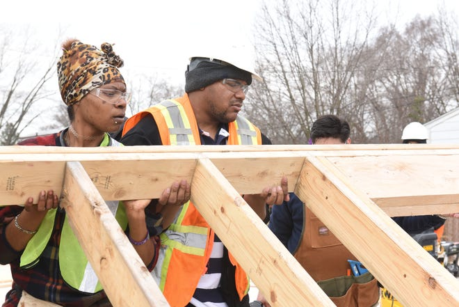 "Marquise Carter, center, and Cierra Stegall lift a framed wall section in a Westland lot on Friday, April 5, 2019, as part of the ""Bridges"" and Youthbuild training program for students."