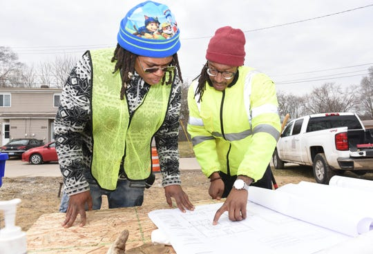 "Instructor Marcus Jones, right, and student Aaron Gaines read building plans at a Westland lot as part of the ""Bridges"" and Youthbuild training program for students."