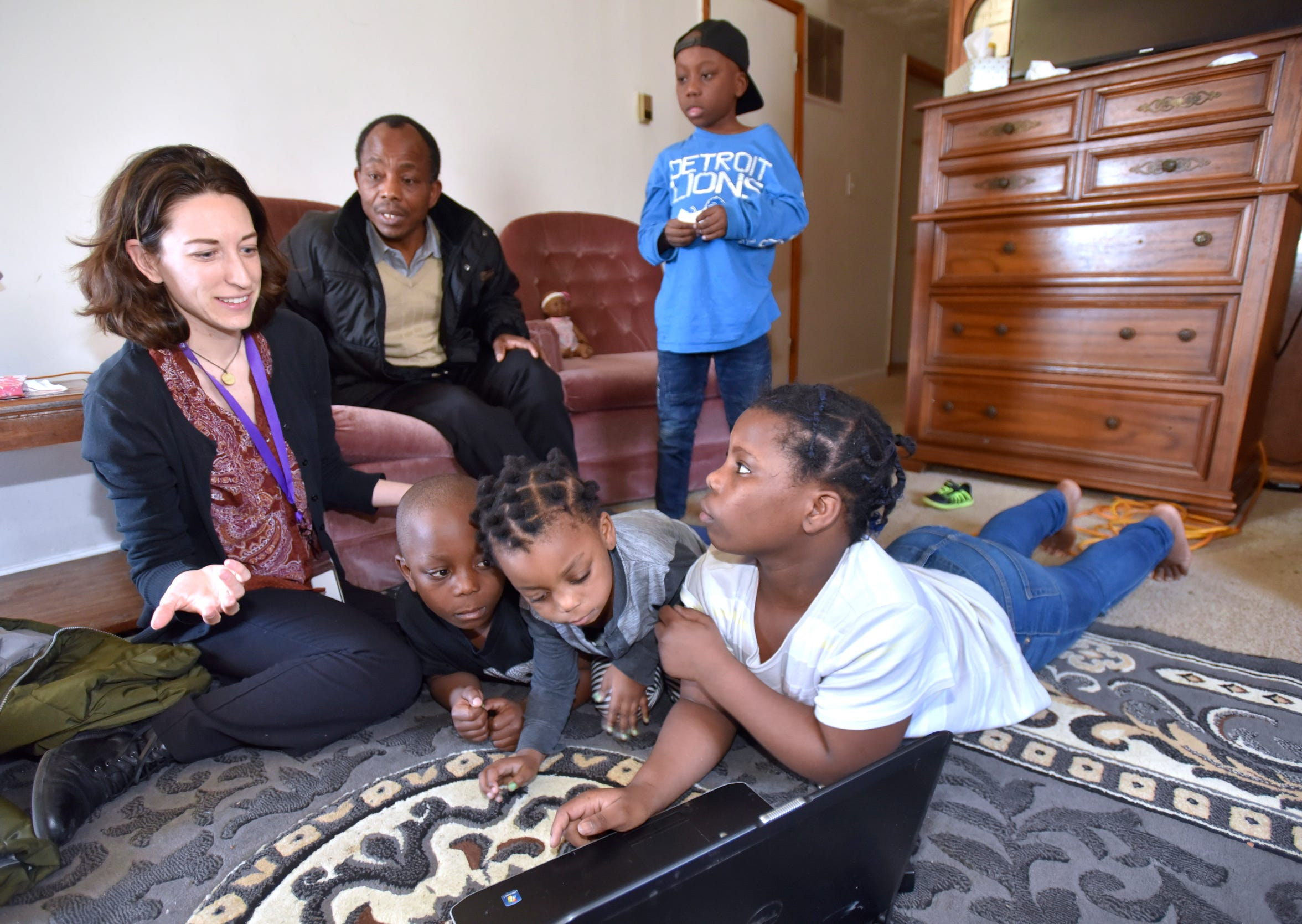 Samaritas' Christina Field, left, supervisor for employment and post settlement for New Americans, tries to fix the track pad on the family computer, to no avail, as Riobert (seated) and his children lie on the floor (left to right) Gido, 6, Estella, 3, Sofia, 12, and Msoshi, (standing), 9, listen.