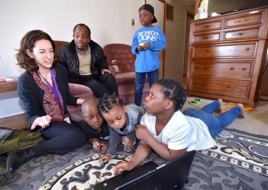 Christina Field, left, supervisor for Refugee resettlement agency Samaritas, talks in 2018 with a resettled family in Warren.