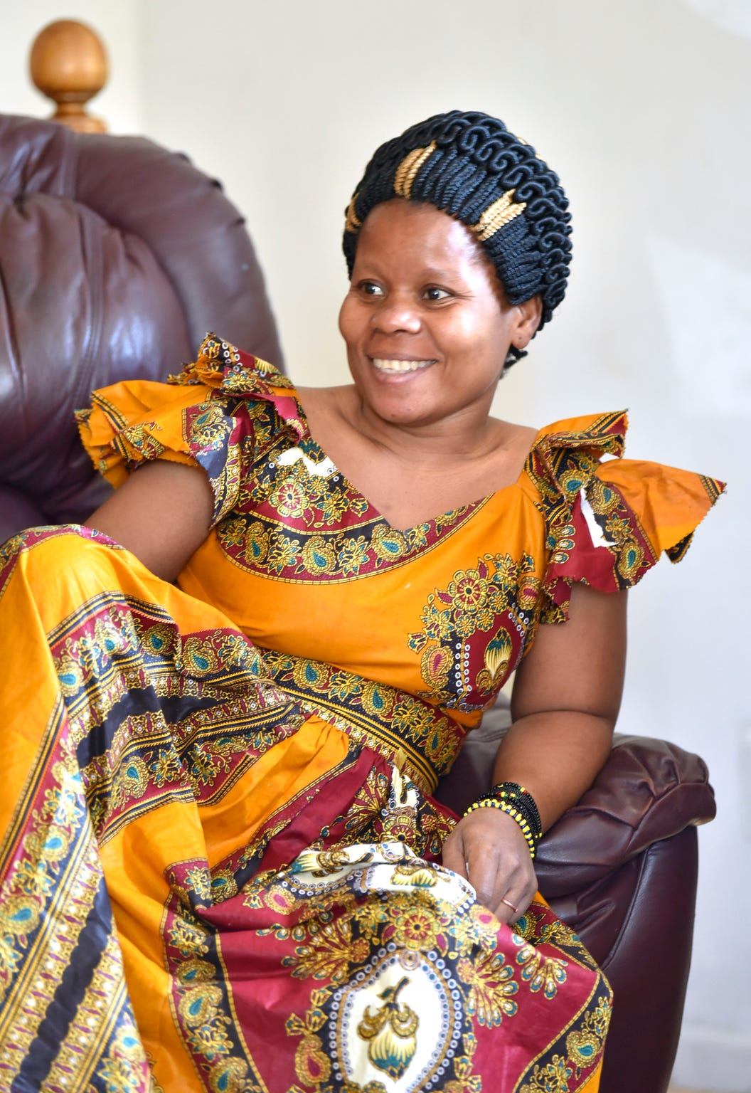 Asende smiles during the interview as she wears a traditional African dress sewn by her husband.