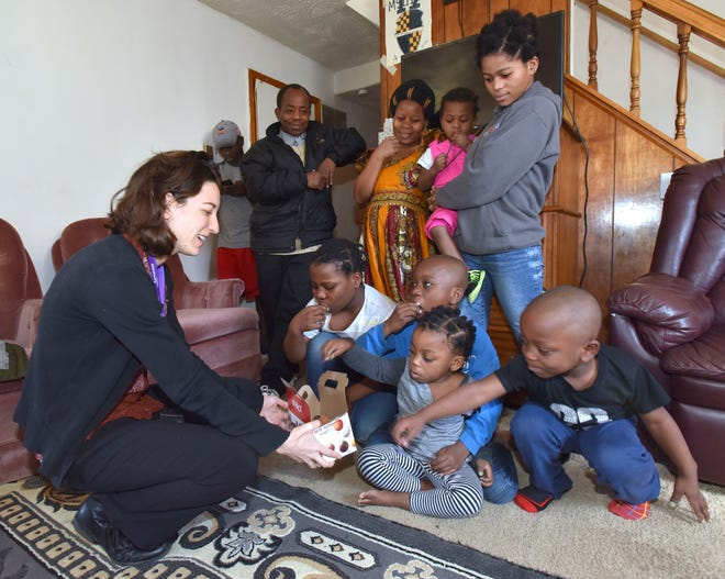 Samaritas' Christina Field, left, supervisor for employment and post settlement for New Americans, offers the children donuts. The Amani family lives in Warren now after spending 20 years in a refugee camp. Despite the few refugees resettling in Michigan, Congolese from the Dem. Rep. of Congo have been resettling in large numbers.