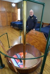 Fred LaPoint of the Manistee Fire Department shows one of two brass poles that allowed firefighters to slide to the main floor to respond to a call. There is a pole on both sides of the living area, allowing crews to slide down to their two engines parked next to the poles on the main floor.