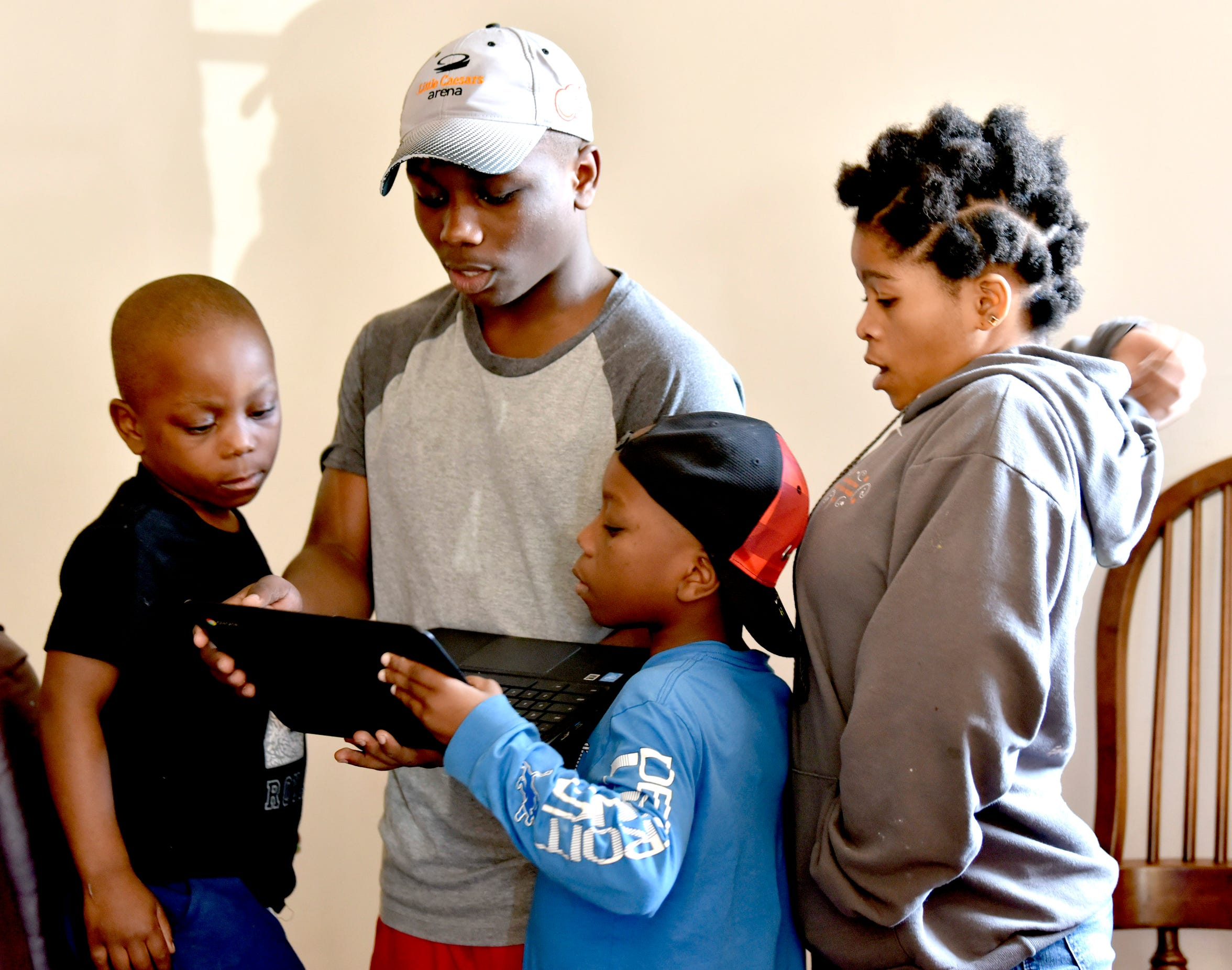(from left) Siblings Gido, 6, Msimbi, 16, Msoshi, 9, and Balongelwa, 19, look at the family computer. The Amani family lives in Warren now after spending 20 years in a refugee camp. Despite the few refugees resettling in Michigan, Congolese from the Dem. Rep. of Congo have been resettling in large numbers.