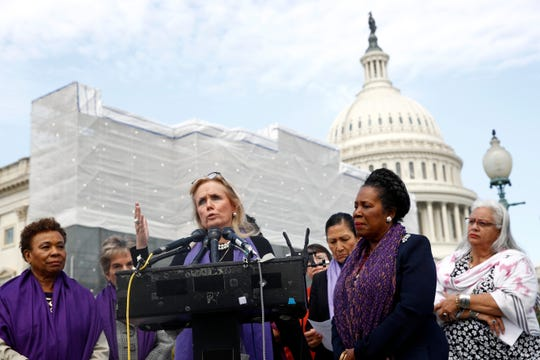 Michigan Rep. Debbie Dingell speaks as Rep. Barbara Lee, D-Calif., left, and Rep. Sheila Jackson Lee, D-Texas, second from right, listen at a news conference after the House voted to reauthorize the Violence Against Women Act, Thursday on Capitol Hill in Washington.