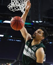 Spartans' Kenny Goins slams home two points during practice.