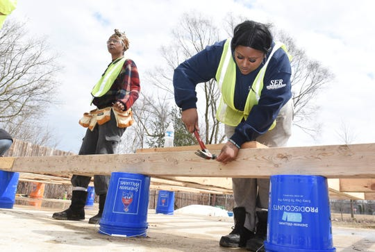 "Carolyn Coleman, right, nails together a framed wall section with fellow student Cierra Stegall in a Westland lot as part of the ""Bridges"" and Youthbuild training program for students."