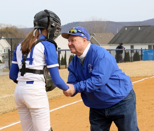 Retired Horseheads softball coach Warren Conklin shakes hands with catcher Maiah Skakal after throwing out the ceremonial first pitch against Owego on April 4, 2019 at Horseheads Middle School.