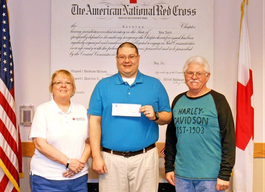 Red Cross volunteer Linda Conway, left, and Tom Doud, right, assistant director of the Arkport-Corning Harley Owners Group, present a $1,500 check from Nation of Patriots to Corning veteran Andrew Scardina.