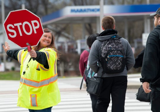 Crossing guard Sandy Mahady does her best to keep traffic stopped to allow students from Bosse High School to cross Hwy 41 at the Washington Avenue intersection Friday afternoon.