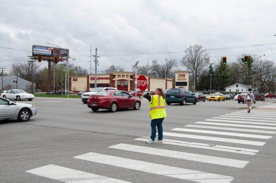 Crossing guard Sandy Mahady does her best to keep traffic stopped to allow students from Bosse High School to cross Hwy 41 at the Washington Avenue intersection Friday afternoon. Two temporary guards were just recently placed at the intersection until permanent guards can be hired.