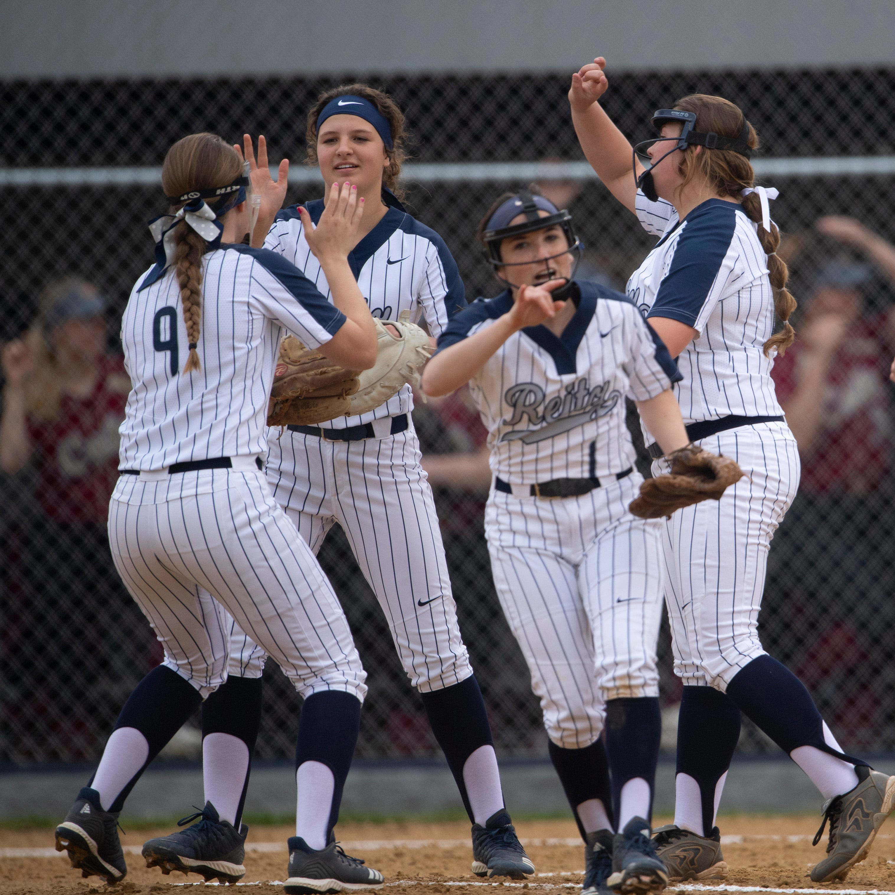 The Reitz infielders celebrate the second out of the first inning against Mater Dei at Reitz Softball Field Thursday evening.