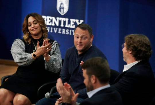 """In this March 5, 2019 photo, panel members including Natalie Baucum, left, applaud Mike Duggan, middle, during an event at Bentley University, in Waltham, Mass., where professors and alumni shared some of their worst setbacks to illustrate that even successful people sometimes fail. A growing number of U.S. colleges are trying to """"normalize"""" failure for a generation of students who increasingly struggle with stress, anxiety and the ability to bounce back from adversity. (AP Photo/Elise Amendola)"""