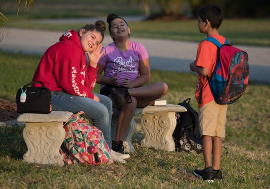 From left, Ava  Pellechio, 10, Carolina Vega, 10, and Zak Woods, 8, all students at Gulf Elementary in Cape Coral, were able to wait for their school bus on a recently installed bench in Melissa Shollack's property. Shollack was so moved after learning about Layla Aiken's hit and run death last month, that she decided to place benches on her property to allow students waiting for the bus in the mornings to sit away from the dangerous roadside.