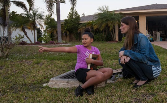 Carolina Vega, 10, speaks with Melissa Shollack Thursday morning, 4/4/19, while waiting for her school bus. Shollack was so moved after learning about Layla Aiken's hit and run death last month, that she decided to place benches on her property to allow students waiting for the bus in the mornings to sit away from the dangerous roadside.