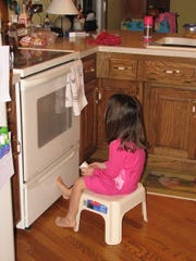 Laura Sullivan at age 4, sitting on a stool in front of the oven watching cookies bake.