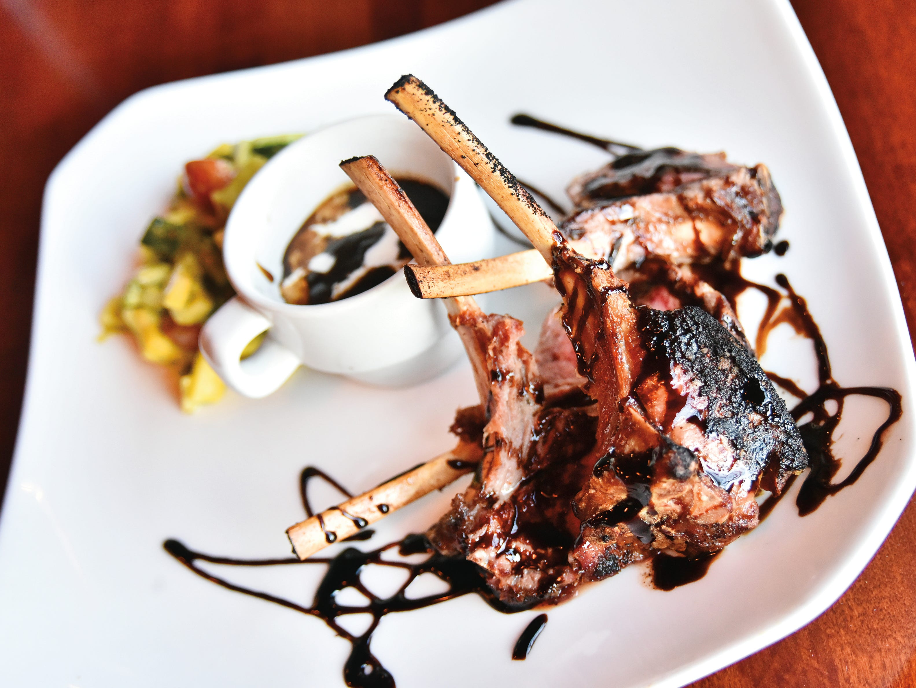 Lollipop lamb chops with an espresso rub, chili infused balsamic, and a side of vegetables in a mint vinaigrette