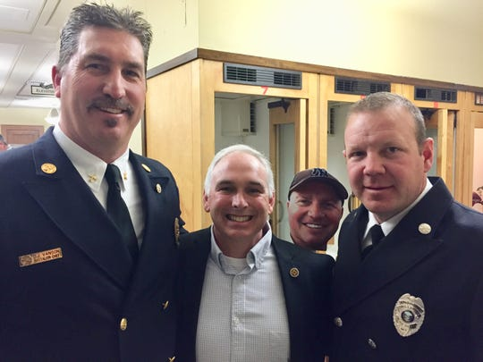 From left, Great Falls Battalion Chief Dave Van Son, Anaconda fire Capt. Scott DeMarois and George Richards, engineer with the Billings Fire Department, pose after Friday's vote on Senate Bill 160. In the background is a profile cutout of Great Falls firefighter Jason Baker, who died from cancer.