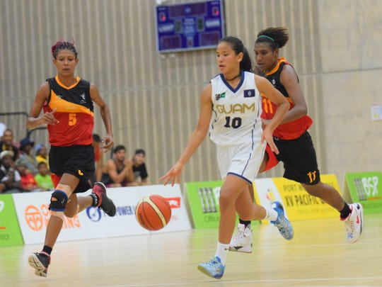 In this 2015 file photo, Guam's Destiny Castro drives to the basket with two Papua New Guinea players in pursuit during their match in the 2015 Pacific Games in Port Moresby, Papua New Guinea.