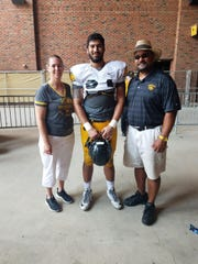 A.J. Epenesa is flanked by his mother, Stephanie, and father, Eppy, following a 2018 open practice at Kinnick Stadium.
