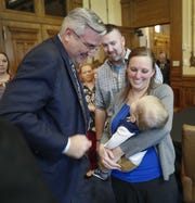 Indiana Governor Eric Holcomb signs the first bill into law in his office on Monday, Mar 25, 2019, at the Indiana State House. Indiana Senate Bill 41, beginning July 1, 2020, screening on newborn babies for detection of Krabbe disease, Pompe disease and Hurler syndrome. Here Governor Holcomb looks at Bryce Clausen, son of Joel and Andrea Clausen, before signing the bill.