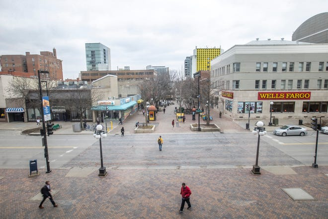 People walk across Clinton Street towards the pedestrian mall on Friday afternoon, April 5, 2019, seen from the Old Capitol Town Center in Iowa City, Iowa.