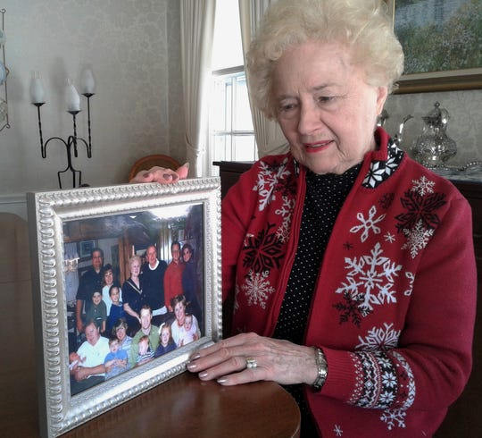 Marjorie Fletcher shows a fond photo of happy family times taken before the death of her husband Bob in the summer of 2000.  He was the subject of a huge three-month manhunt in this area until he was found deceased in his car underwater in a Lake Macbride cove.