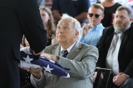 John Allman, James P. Shaw's nephew, receives an American flag in honor of his uncle's sacrifice in Biloxi Friday.