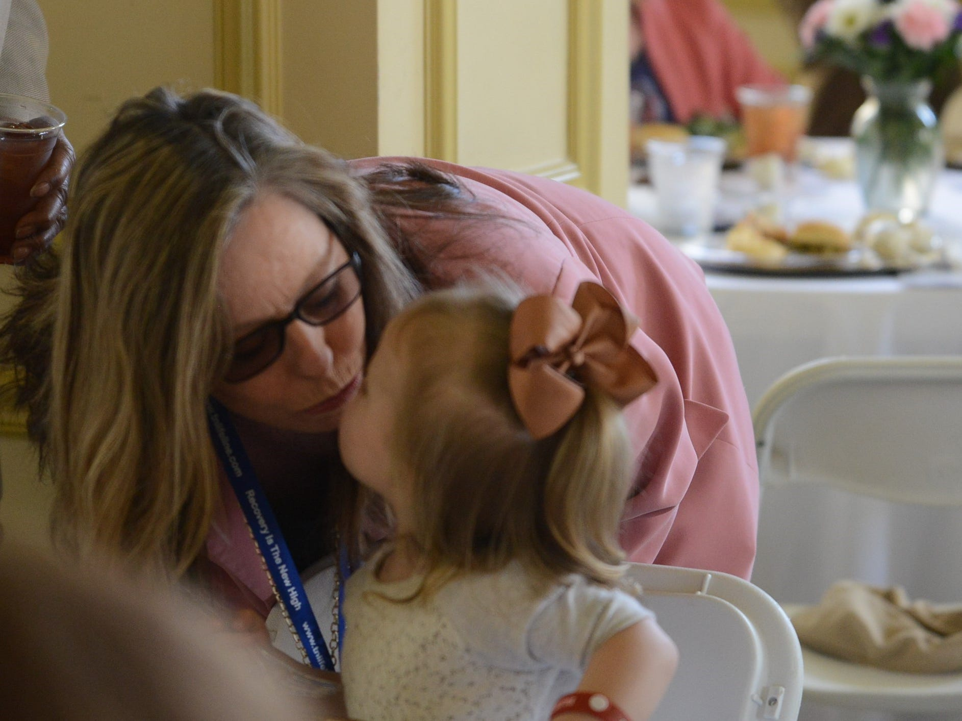"Dianne Sherrod, Project Lifeline Coordinator, stops to kiss Faith Osborne at the Jackson Recovery Court graduation luncheon at the New Southern Hotel on Wednesday, April 3. Osborne's mother was a house monitor at the care center and serves as a mentor to those in Recovery Court. Sherrod says she is one of their ""success stories."""