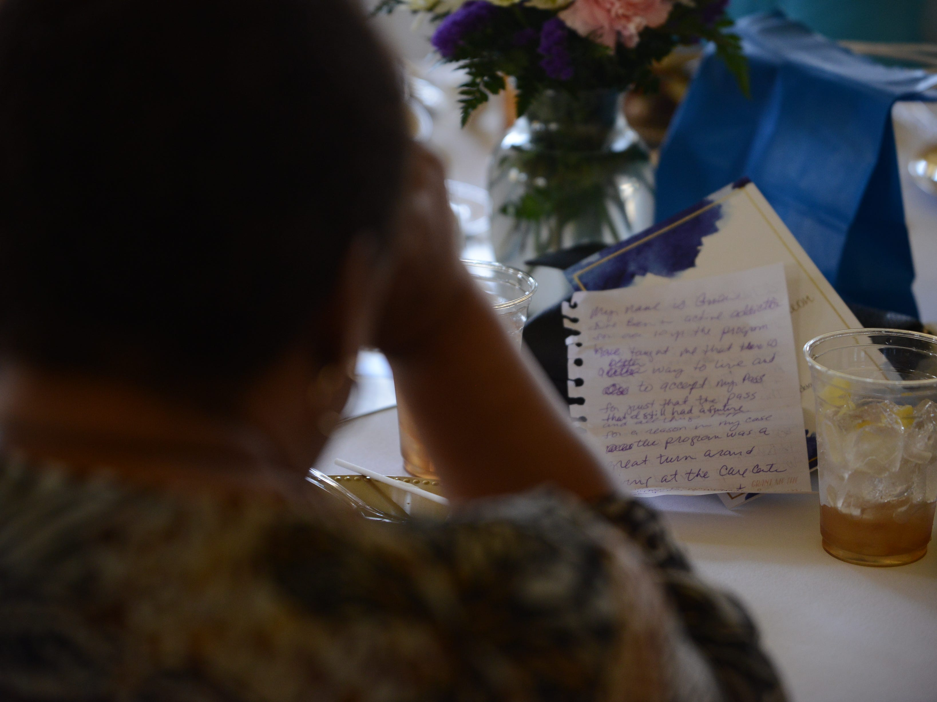 Carma Northern bows her head in prayer at the at the Jackson Recovery Court graduation luncheon at the New Southern Hotel on Wednesday, April 3. Northern came to support friend and program graduate Gwen Woods. Wood's notes for her speech rest on the table in front of Northern.