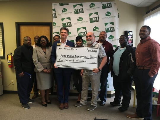 Michael Roby and the staff and board members at Area Relief Ministries accept a check for $100,000 from Junior Johnson on behalf of the Leon-Alavine Harris trust fund.