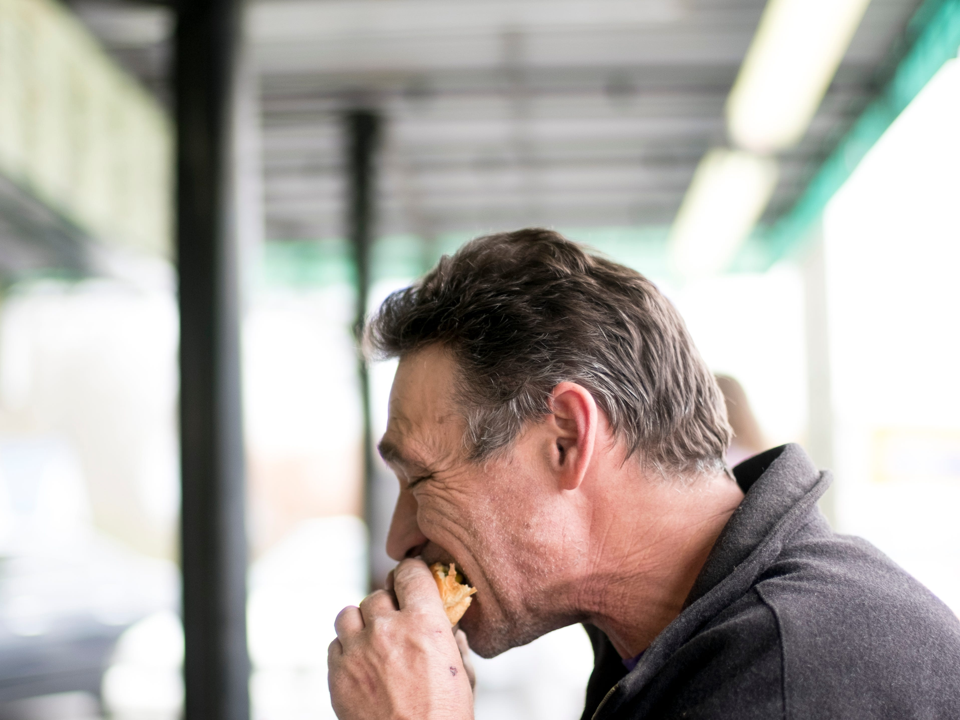 Richard Miller takes a bite of his burger during a stop at Cardin's Drive-In on Asheville Highway in Knoxville, Tennessee on Friday, April 5, 2019. The popular drive-in is celebrating 60 years of business this Saturday with sixty cent ice cream cones.