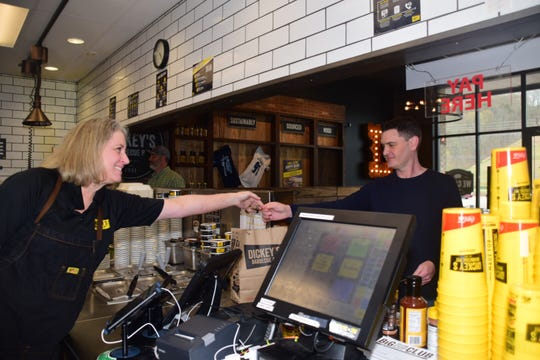 """Owner Barbara Hall hands Chad Heird of Hardin Valley his order, the Western sandwich – the Wednesday special at Dickey's Barbecue Pit.  """"We love this place. It's delicious and quick and easy,"""" said Heird. April 4, 2019"""