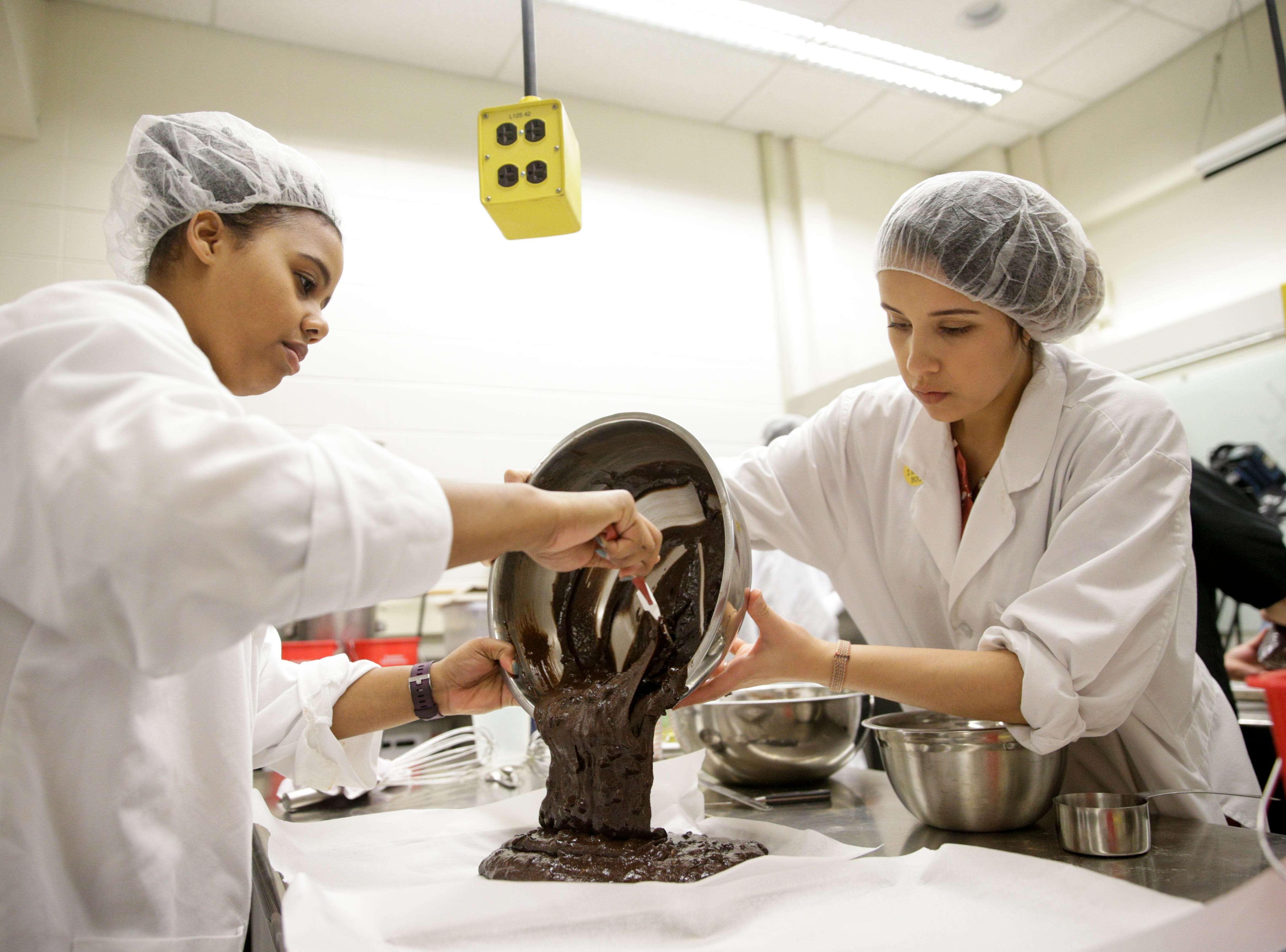 Gabriela Calzada, right, helps Felicia Hall pour cricket brownie batter onto a tray, Friday, April 5, 2019, at Purdue University in West Lafayette. The brownies and other insect incorporated dishes will be served during Saturday's Spring Fest.